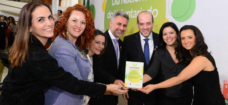 Equipe da Fundação Telefônica Vivo recebe Prêmio Viva Voluntário e posa para foto segurando objeto