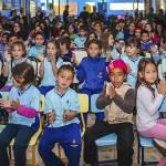 Crianças uniformizadas sentadas batem palmas