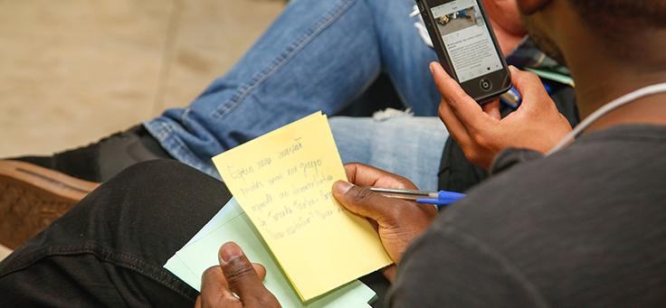 Pessoa segura bloco de notas com uma mão e na outra uma caneta