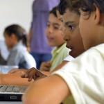 Duas crianças olham para a tela de um computador em sala de aula