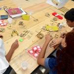Três jovens em volta de uma mesa no Lab Maker Arrastão
