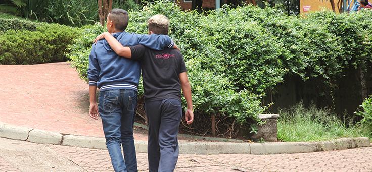 Duas crianças andam abraçadas