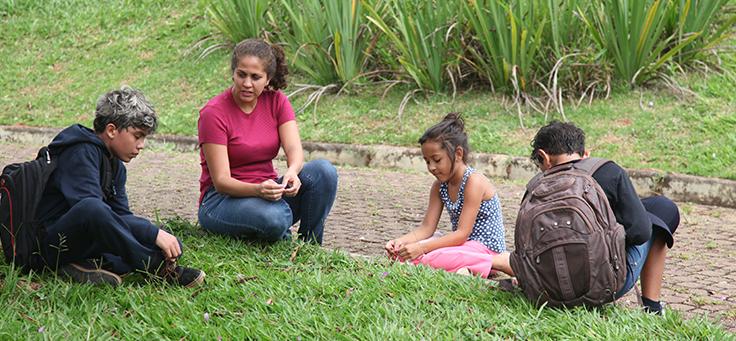 Adulto conversa com três crianças em roda de conversa na grama