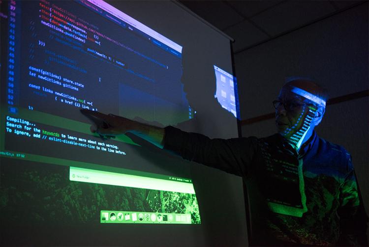 Homem de meia idade aponta para dados projetados sobre tela em apresentação