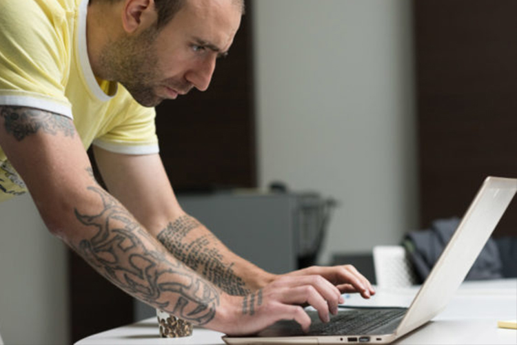 Foto de perfil de homem debruçado sobre mesa usando notebook