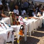 Expositores da feira afro meninas mahin, apoiados pelo Fundo Zona Leste Sustentável. Na foto, há várias mesas de plástico perfiladas, com produtos como camisetas e bonecas na temática afrobrasileira