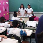 Foto mostra sala de aula a partir dos fundos, com alunos sentados em carteiras, de costas, e duas alunas de origem boliviana de pé, na mesa onde fica a professora, de costas pra lousa e de frente pros colegas, durante apresentação