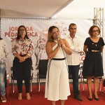 """Grupo de pessoas em pé em frente a um banner onde se lê """"Jornada Pedagógica"""". Uma moça de macacão branco está falando ao microfone."""