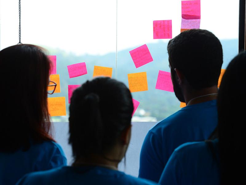 Voluntários olham post its colados em vidro