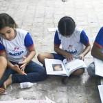 Seis crianças do Projeto Cemar sentam-se no chão para brincar