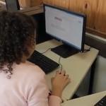 Duas crianças alunas da EMEF Amorim Lima sentadas em frente a um computador