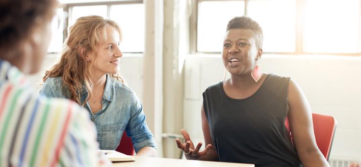 Mulher negra sentada de frente, loira de lado e uma pessoa de costas conversam