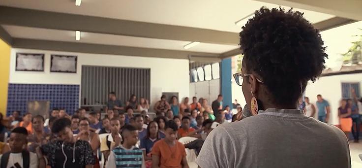 Muher negra de costas olha pra plateia sentada. Ela usa coque e óculos