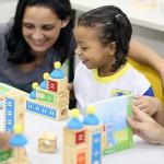 Professora e criança brincam com objeto de madeiras em mesa de escola