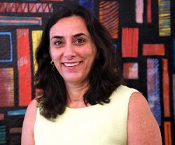 Coordenadora de Educação da Unesco, Rebeca Otero. Morena, cabelo nos ombros, pele clara. Fundo tem quadro colorido com formas geométricas