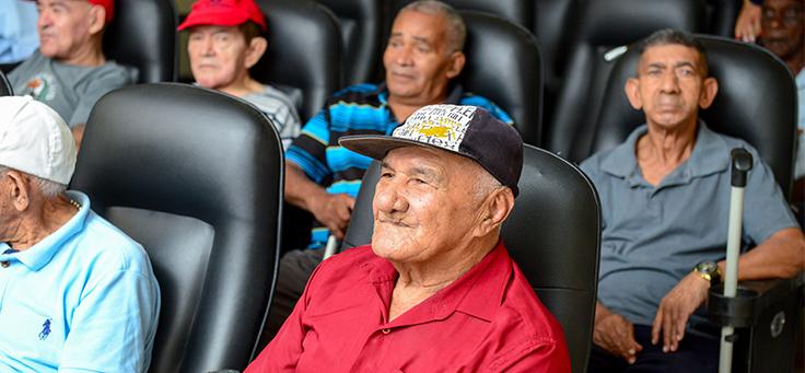 Imagem mostra parte de uma plateia do cinema instalado na Casa dos Velhos Irmã Alice. Seis idosos aparecem sentados, olhando com atenção para a tela.