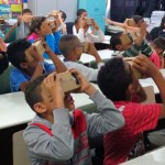 Crianças em sala de aula sentadas em suas carteiras usam Google Cardboard, óculos de realidade virtual com estrutura de papel craft e baixo custo.