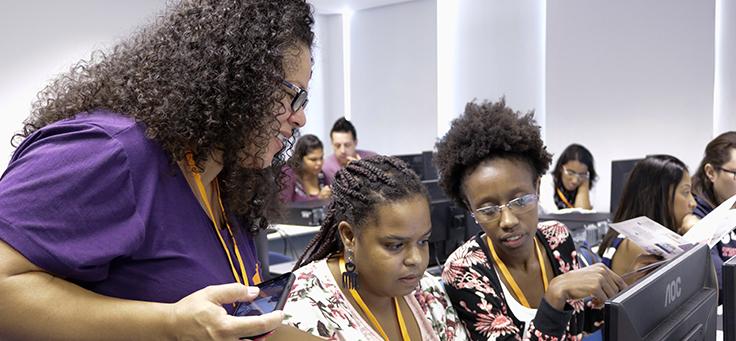 Imagem mostra três mulheres olhando para a tela de um computador