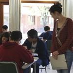 Imagem mostra professora em sala de aulas com alunos sentados em grupos