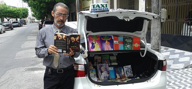 Na imagem, o taxista Carlos Careca lê um livro em frente ao seu táxi, batizado de bibliotáxi