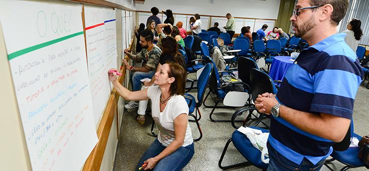 Na imagem, participantes de encontro estão em pé e escrevem em cartazes afixados nas paredes em uma sala