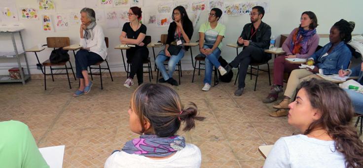 Imagem mostra pessoas em sentadas em roda em projeto sobre voluntariado como ponte entre o refugiado e seu novo país