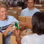 Imagem mostra duas pessoas atuando como voluntárias. Uma delas aparece sorrindo