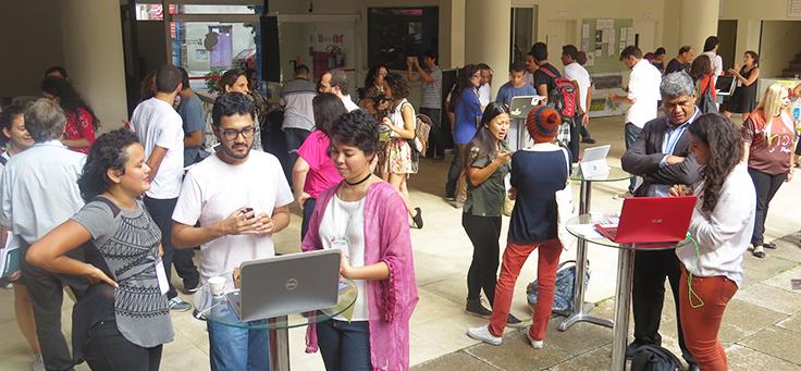 Foto mostra vários grupos de jovens conversando em volta de computadores