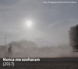Na imagem, pessoas andam em meio a poeira levantada por caminhão em cena do documentário Nunca me Sonharam