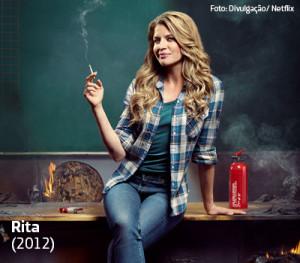 Professora Rita aparece sentada em uma mesa e fumando cigarro em cena da série da Netfilx