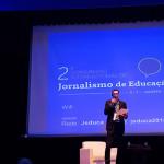 Antônio Gois, presidente do Jeduca, está em pé no palco e com microfone na mão durante a abertura do 2º Congresso Internacional de Jornalismo de Educação