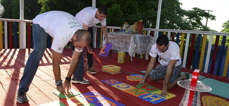 Voluntários pintam chão da escola durante o Vacaciones Solidárias em Manaus