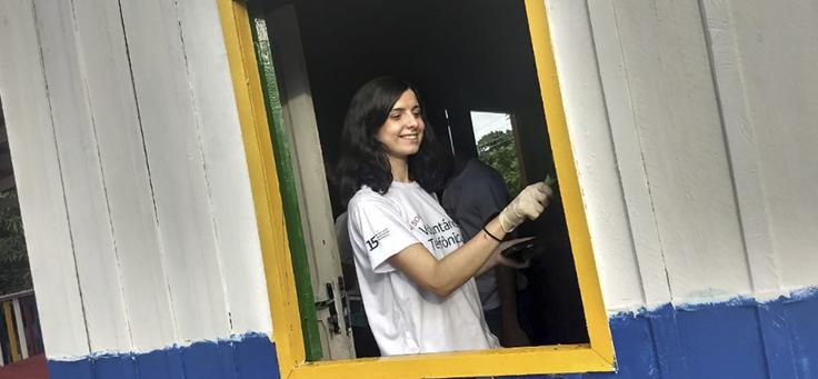 Voluntária pinta janela da escola durante o Vacaciones Solidárias em Manaus