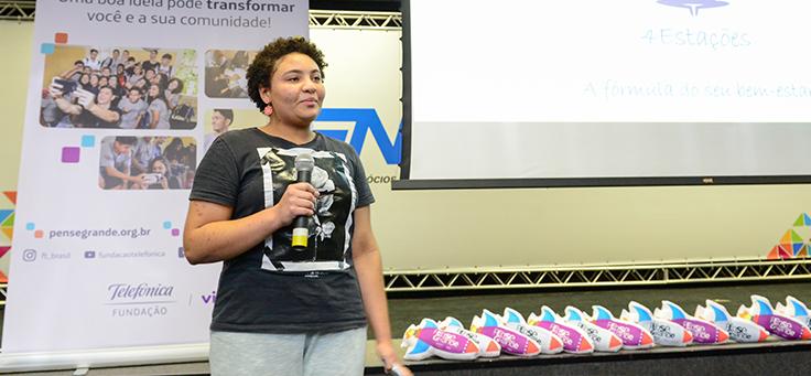 Na imagem, a estudante Cecília Ribeiro de Almeida, de 15 anos, aparece em pé com microfone na mão e sorrindo durante apresentação do projeto dela, o 4 Estações