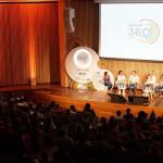 Na imagem, seis palestrantes estão sentados em roda em cima do palco durante o evento Educação 360