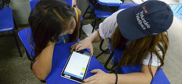 Pessoa com camiseta do Vaciones Solidarias, projeto de voluntariado internacional, usa tablete ao lado de criança
