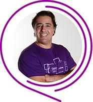 Na imagem, o voluntário Alexandre de Souza Pinto posa de braços cruzados e usando camiseta púrpura do Programa de Voluntariado. Ele tem cabelos pretos e sorri para a foto