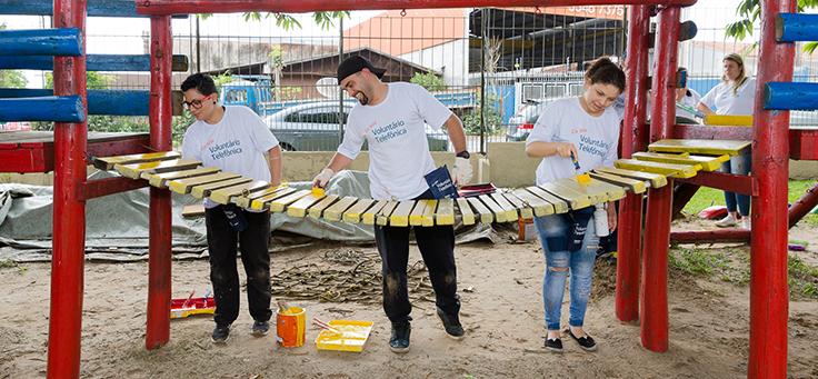 Três colaboradores pintam parquinho de criança durante o Dia dos Voluntários