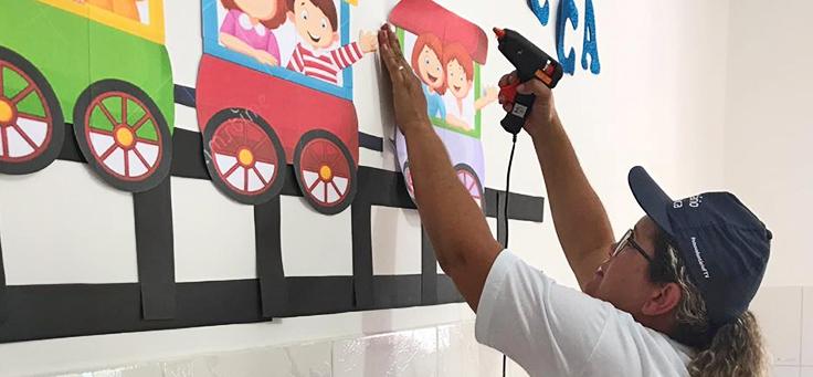 Colaboradora afixa mural durante o Dia dos Voluntários
