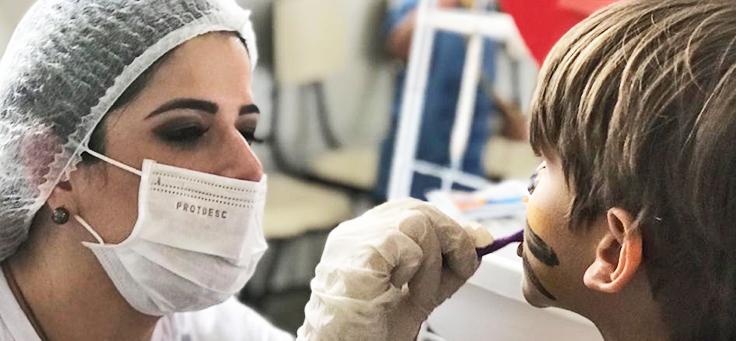 Voluntária verifica dente de criança durante dia dos voluntários