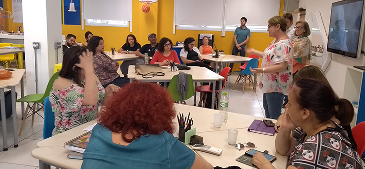 Professores estão na sala de aula, em pé e sentados, participando de uma atividade do Encontro de Integração.