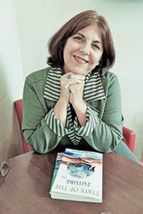 A especialista Rosa Alegria está com as mãos sob o queixo e com os braços apoiados em uma mesa. É possível ver sobre a mesa o livro State of the Future