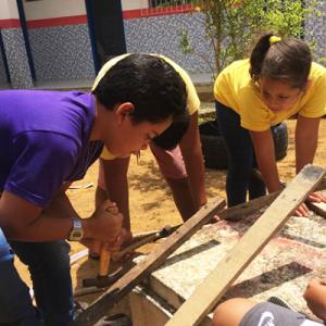 Duas crianças, um menino de camiseta azul e uma menina de camiseta amarela, mexem com pedaços de madeira