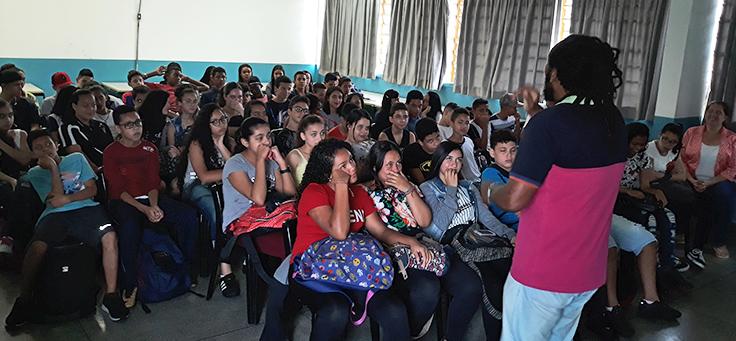 Alunos estão sentados em carteiras olhando para palestrante, em atividade promovida pelo Quero na Escola