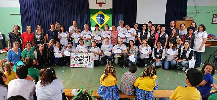 Voluntários e funcionários da Escola Primavera posam para foto em grupo.