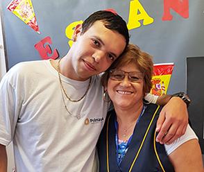 Rapaz de camiseta branca, abraça a professora Ana Martins, que está de colete azul. Ambos sorriem para a foto.