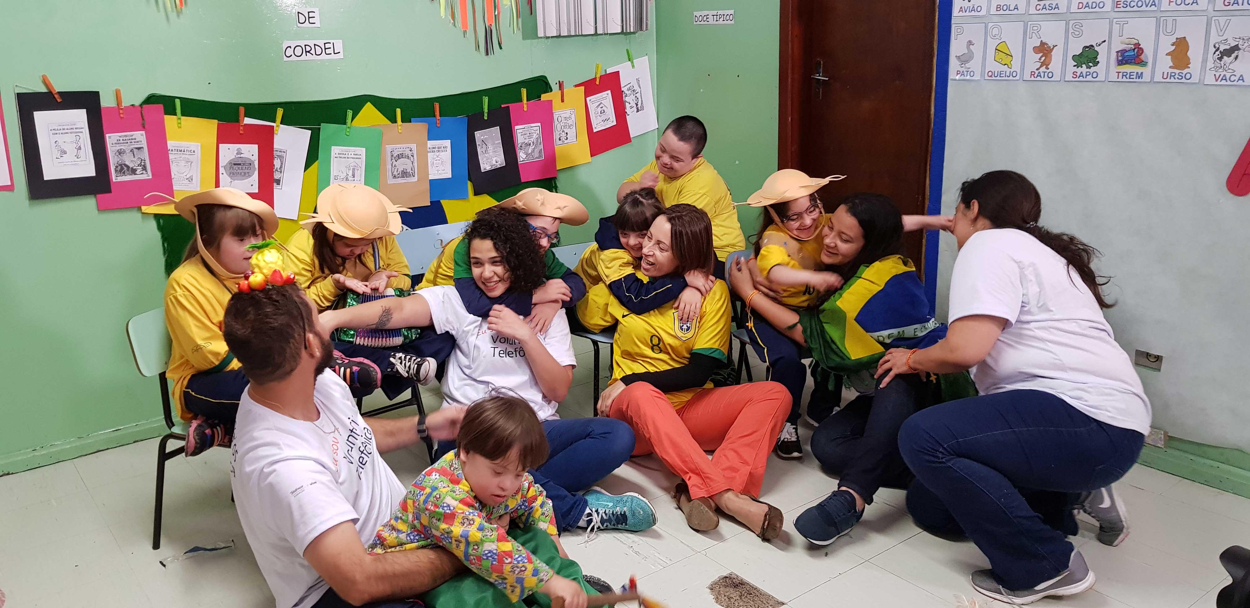 Sentados no chão de uma sala de aula, quatro voluntários estão cercados por crianças sorridentes e abraçados por elas.