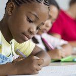 Na imagem, aluno escreve em caderno, sentado em carteira, para ilustrar matéria sobre educação brasileira