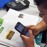 Na imagem aluno de projeto que alia leitura, tecnologia e pesquisa utiliza smartphone. Ele apoia as mãos em um livro didático.