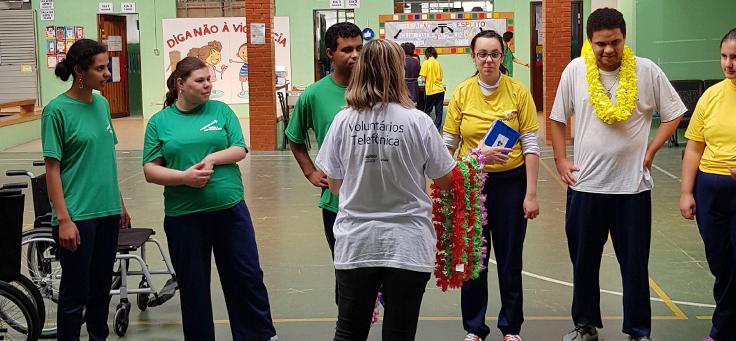 Na imagem tutora está segurando colares havaianos diante de grupo de alunos da Escola Primavera durante dinâmica sobre programação
